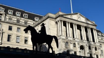 The Bank of England is seen, with a statue in the foreground, in the City of London