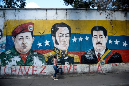"""An electoral propaganda graffiti depicting late Venezuelan President (1999-2013) Hugo Chavez (L), South American independence hero Simon Bolivar (C) and Venezuelan President Nicolas Maduro on a wall of the Petare shantytown in Caracas on December 1 , 2015. Sixteen years into late president Hugo Chavez's leftist """"revolution,"""" opinion polls indicate the opposition is poised to win legislative elections Sunday for the first time since the firebrand leader came to power.  AFP PHOTO/FEDERICO PARRA / AFP / FEDERICO PARRA        (Photo credit should read FEDERICO PARRA/AFP/Getty Images)"""