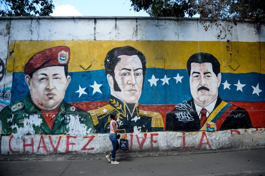 "An electoral propaganda graffiti depicting late Venezuelan President (1999-2013) Hugo Chavez (L), South American independence hero Simon Bolivar (C) and Venezuelan President Nicolas Maduro on a wall of the Petare shantytown in Caracas on December 1 , 2015. Sixteen years into late president Hugo Chavez's leftist ""revolution,"" opinion polls indicate the opposition is poised to win legislative elections Sunday for the first time since the firebrand leader came to power. AFP PHOTO/FEDERICO PARRA / AFP / FEDERICO PARRA (Photo credit should read FEDERICO PARRA/AFP/Getty Images)"